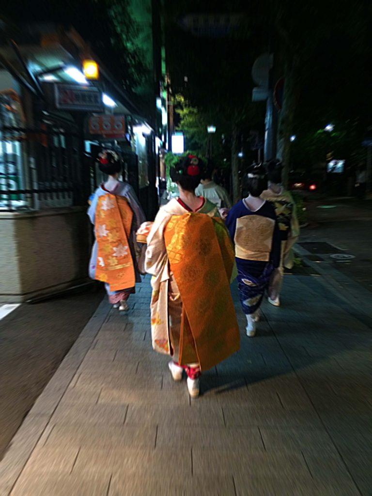 Two maikos (novice giesha) and their seinor geishas walking down the night street