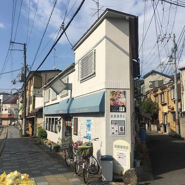 早朝5時過ぎに東京からの夜行バスで京都に着いた友達を5時45分ごろJR花園駅で拾って「さあてモーニングでも」という話になったが、そんな時間に開いている喫茶店など思い浮かばず、その辺りにはコンビニのイートインくらいしか選択肢がなかった。ところが「早朝、右京区、モーニング」と検索すれば出てくるもので、JR嵯峨嵐山駅ちかくに6時からやっている「廣瀬(ヒロセ)珈琲店 」ってのが引っかかってきた。しかし、写真は僕らがあまり行かないオーソドックスな、まあ言ってしまえば何の変哲も無いファサードで、これは、さて如何なものか、、、と二人で思案。ま、コンビニよりはいいか、、、と、ちょっと西へ足を伸ばした。ただ、場所は判るが駅で行き止まりの道にあり、普段めったに通ることはない。そんな喫茶店あったっけ、、、みたいな感じで一抹の不安を抱えたまま車を走らせた。果たして件の珈琲店は横尾忠則が喜びそうなY字路の上に建っていた。外観も写真で見たとおり。入る前から内装は想像がついた。昭和の時代の由緒正しい「喫茶店」。 ドアを押し開いて足を踏み込んで、その予感は全く正しいことがわかった。モーニングのメニューも、もう注文前に脳裏に浮かぶ。ただ、店のマスターが僕より歳上のようだったこと、それに一番乗りだと思った僕らよりも早く、すでに店内のカウンターの椅子に掛けていた数人の常連客もおしなべて僕よりも上のようだったことは想像だにしていなかった。時とともにさらなる老人の流入が続く。店内が思いの外明るいのは、単に店が外東向きで店内陽がよく差し込む以上に、元気な老人たちの会話によるものだと思う。ここは当たりだ!と二人でニンマリする。店の前から見える駅がまだ「嵯峨駅」とか「国鉄嵯峨」と呼ばれていた頃からずっと、店も 主人も客も一緒に歳をとってきたのに違いない。大きなクロスゲーブルを構えた瀟洒な洋風木造駅舎はとっくに建て替えられても、お構いなしに廣瀬珈琲店の中は「昭和」の空気を閉じ込めているようだ。(本当は平成の開業なのかもしれないが、、、) この店に「レトロ」という言葉は当てはまらない。レトロとはRetrospective、つまり「回顧的」、「懐古的」という意味だが、それは今を生きる人間が過去に目を向け、懐かしがって模擬的に過去を再現した「昔風」ということ。でも廣瀬珈琲の内部空間とそこに集う人たちは「風」なんてもんじゃない。彼らは過去から生き続け、今も生きているガチでリアルな老体なんだから、紛れもなく「本物」だわ。リアルな老体であればあるほど、今を生きる老人たちは、はてさて未来へどこまでその歩を進め、持ちこたえてくれるのだろうか、、、 僕と友人はせっかくこうやって「好みの店」を見つけても、ある日突然その店が閉じてしまう寂しさを何回経験してきたことか。じじばば、元気でいてよ〜! (from Instagram)