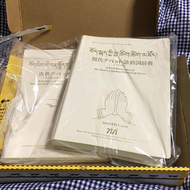 長らく探していた口語チベット語の辞書『現代チベット語動詞辞典 (ラサ方言)』が手に入った。17〜8年前に星泉さんが著して今も評価の高い辞書だが、気づいたときには在庫が無くなっていた。もともと発行部数が少なかったので古書として出てくることも滅多にない。たまにヤフオクとかに高額で出品されていたようで、少々高くても落札したかったが行き当たったことがなかった。それが偶然、数年前に増刷されていたと知ったのはほんの4日前。また乗り遅れたか、と思ったけど、ダメ元で問い合わせみてみたら「在庫あり」とのこと。さらに、オマケと言う訳ではないが、『古典チベット語文法:『王統明鏡史』(14世紀) に基づいて』と言う星泉さんの新刊も配布されていて、どちらも無料でいただけるとのこと。早速「東京外国語大学アジア・アフリカ言語文化研究所多言語・多文化共生に向けた循環型の言語研究体制の構築(LingDy3)事務局」と言う恐ろしく長い名前の配布を元に申し込んだ。どういうわけか研究者・大学関係者と勘違いされて送料も免除と連絡があった。チベット研究をやっている知り合いの大学教授と共同編集した大学の刊行物がいくつかあるので、僕まで研究者だと思われたのだろう。チベット関係に限らず、大学や研究所はどこも予算が逼迫している昨今、配布元がそう言ってくれてもこれ幸いと無料でもらうわけにはいかない。丁寧にお断りして、着払いで送っていただいた。今朝届いて、箱を開けるのももどかしくワクワクしながら手に取って、辞書と文法書を開いた。日本のチベット語研究は仏教を通じて始まったので、古い辞書や文法書はどちらかと言うととっつきにくいものが多いが、送ってもらった2冊はずいぶん様相が違っている。かといって旅行者用の簡易な会話手帳のようなものでももちろんない。星泉さんのお母さんの星三千代さんのチベット語入門書も読んだことがあるが、其処此処に「受け継がれた伝統」のようなものを感じる。 (from Instagram)